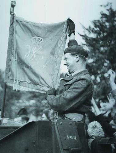 Vol trots tonen de mannen het vaandel wanneer ze Den Haag binnenrijden